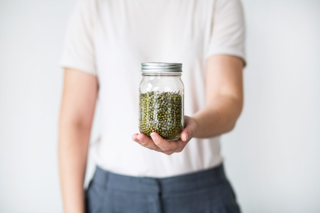 person holding clear glass jar with green peas in it