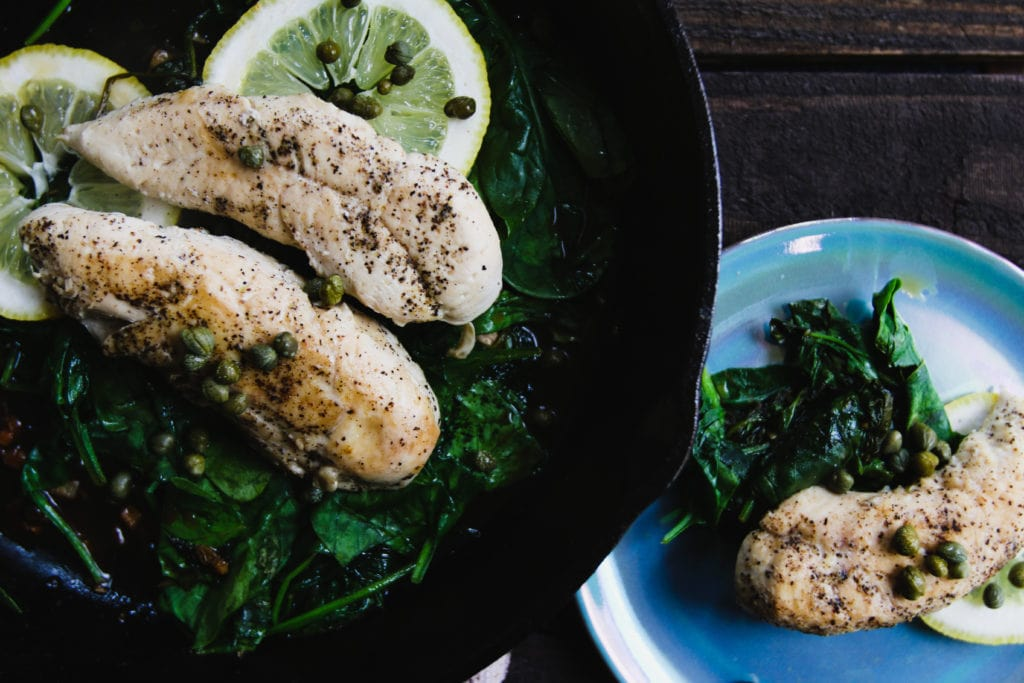 lemon caper chicken and garlic spinach on plate