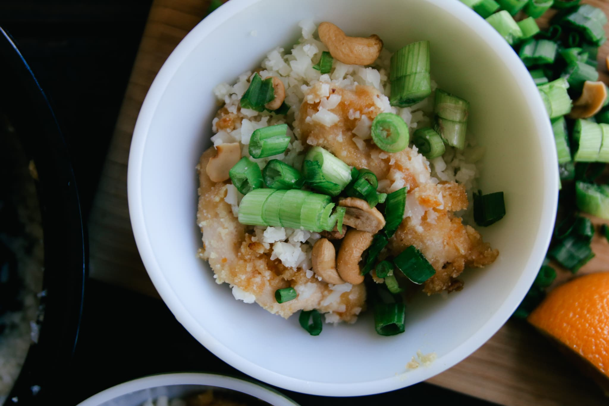 cashew orange chicken cauliflower rice green onions in a bowl