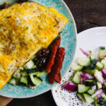 greek omelet on plate with olives and tomatoes
