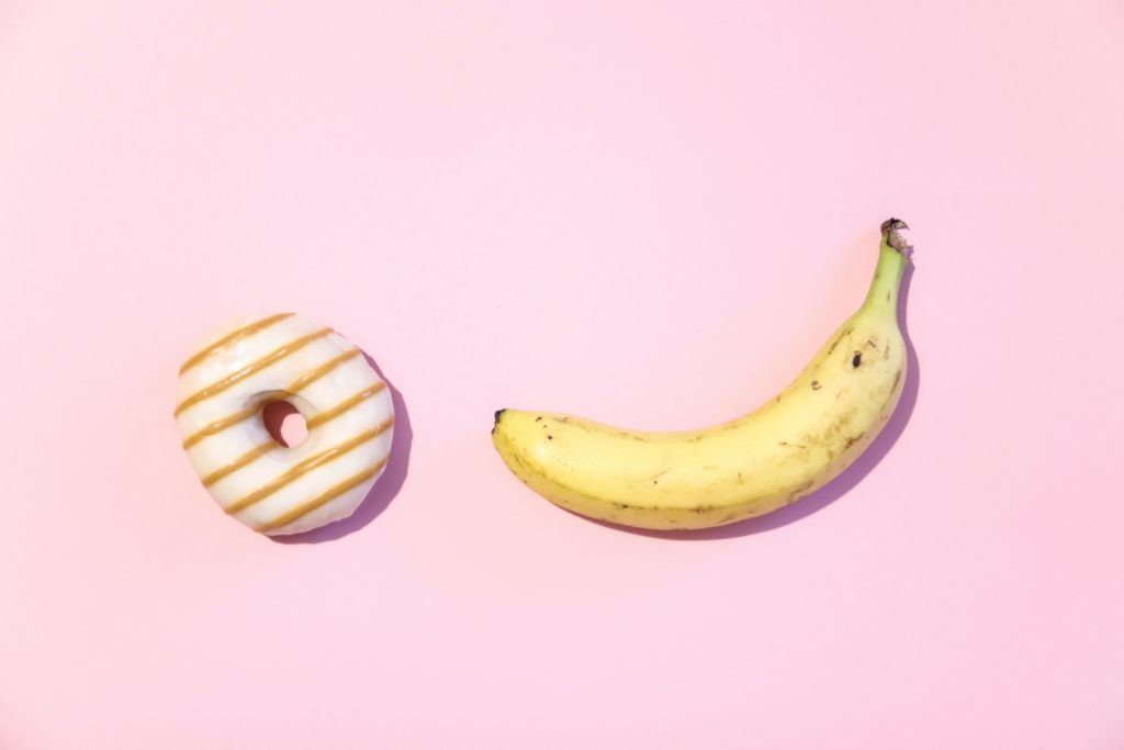 banana and donut on pink background