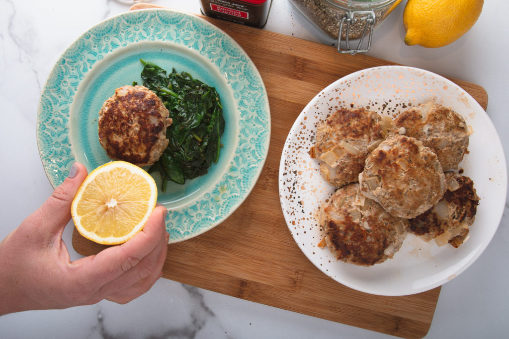 turkey sausage patties and spinach on plates with a hand holding a lemon